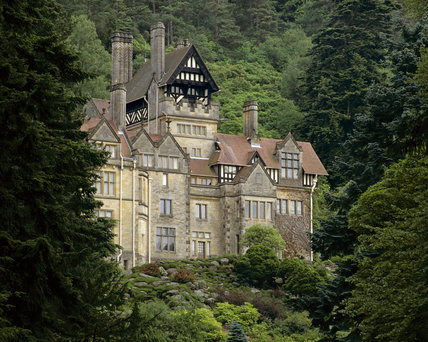Close view of the south end of the west elevation of Cragside with dense forest above and the glen below, showing details of elevation including chimney stacks and pitched and tiled roofs