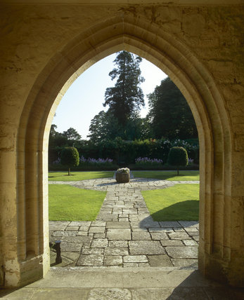 View from archway of the house of part of the Forecourt with stone slab paths, lawns and bay trees at Nymans Garden, W