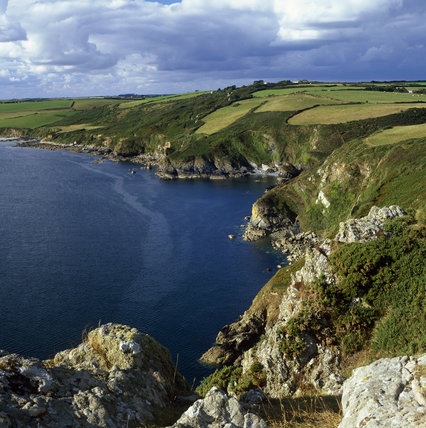 Looking onto the west side of the craggy Nare Head, Cornwall, with the rocky cliffs stretching away in to the distance