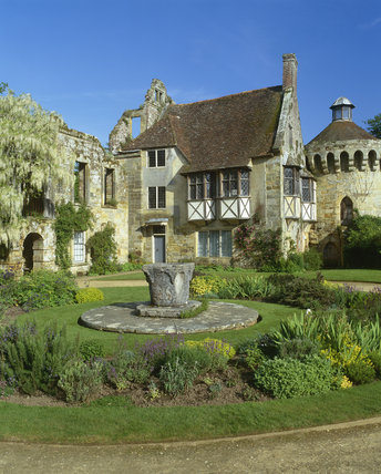 The well-preserved 14th century Ashburnham Tower at Scotney Castle attached to the mainly ruined castle seen across the herb garden that surrounds the stone Venetian well-head