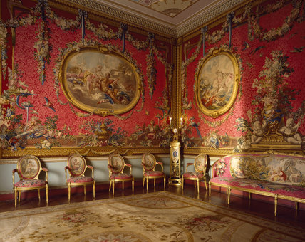The Tapestry Room at Osterley Park designed in the C18th by Adam for Robert Child, showing Boucher's medallion tapestries with a sofa and chairs upholstered in rose damas cramoisy to match the walls