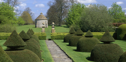 The Apostle Garden at Lytes Cary Manor takes its name from the twelve yew bushes that line the front path, with the water tower at the end built in imitation of Avebury Manor dovecote