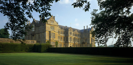 The east front of Montacute House taken from an angle across a lawn showing the oriel window which finishes the southern end of the Long Gallery on the south-east front, photographed at dawn