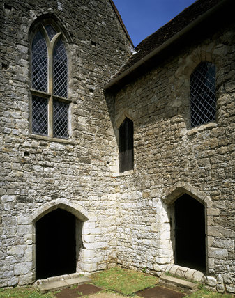 A close up view of a corner of the Old Soar Manor, showing two arched windows and three arched doorways, one being half way up the building in the corner