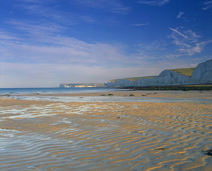 Looking across the sandy beach, rippled by the retreating tide, with the white cliffs of Birling Gap as a back drop
