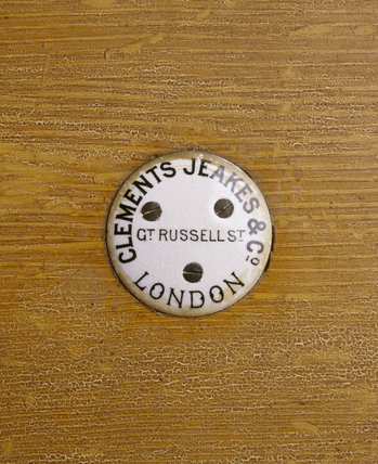 Close view of a ceramic plaque with the name and adress of the contractor for the kitchen fittings provided for the mordenisation of Dunham Massey in 1906