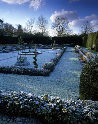 The Dutch Garden at Clandon Park in winter, with light snow under frost