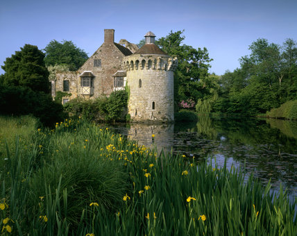 The circular 14th century Ashburnham Tower at Scotney Castle with irises growing in the moat in the foreground and the later ruins behind