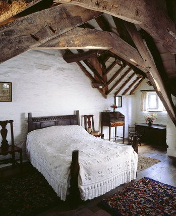 The South Bedroom in the Old Post Office at Tintagel, showing restored beams, snip rugs, a wooden chest, tall desk and stone hot water bottle, all typical in the 19th century