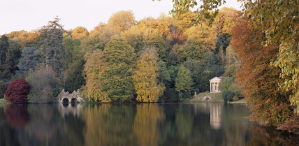 View across the lake of The Temple of Flora amongst the Autumnal foliage of the trees at Stourhead