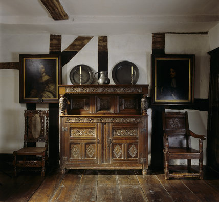 A 17th century carved oak court cupboard in Mr. Whitgreave's Room at Moseley Old Hall with a pewter mug & platters on top. The portraits are of Charles II and his wife, Catherine.