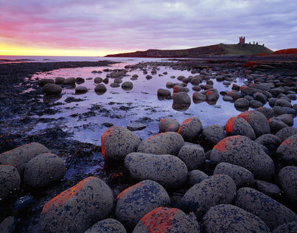 View of Dunstanburgh castle from the north west taken at first sunlight at dawn during the march (spring) Equinox