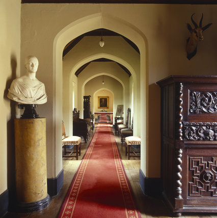 Room view from the entrance showing the Corridor at Oxburgh Hall The view shows the carved wooden furniture, a marble bust and the arches of the hallway