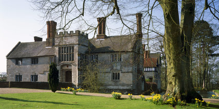 Front elevation of Baddesley Clinton, a 15th century stone house with mullion windows, tall chimneys and a central gatehouse