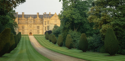 Long view of the front of Montacute House showing curved drive with grass, yew bushes and trees on either side