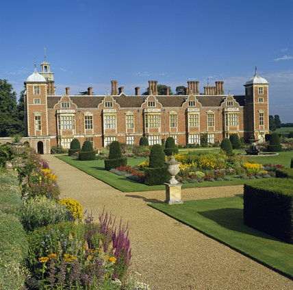 The north front of Blickling Hall seen across neatly trimmed lawns, paths and colourful flower borders