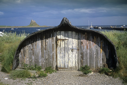 An old converted ship's hull on the edge of Holy Island Harbour, surrounded by rushes and grass, with the Castle on the horizon