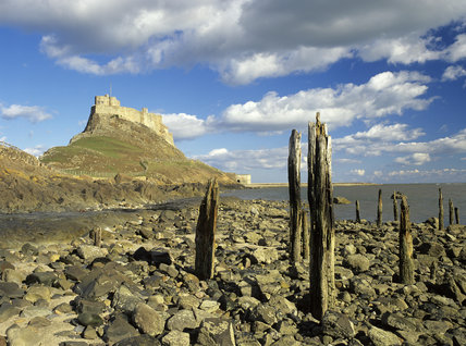 Lindisfarne Castle on Holy Island standing on the high rock, against the cloud flecked sky