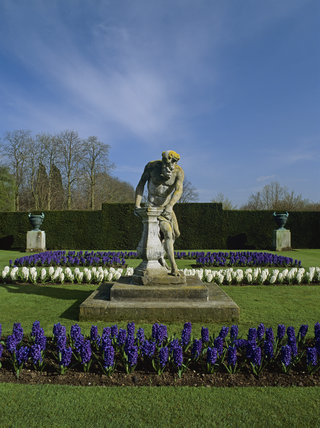 The Father Time Sundial in the Hyacinth Garden at Anglesey Abbey surrounded by a glorious display of white and blue hyacinths