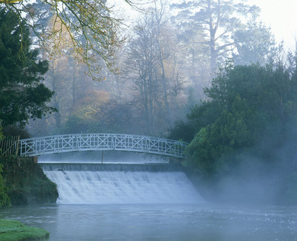 A cascade and bridge between two lakes in Sheffield Park, the early morning sun penetrating the mist creates an eerie picture