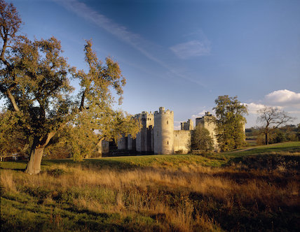 Bodiam Castle exterior seen from across the fields in warm autumn light