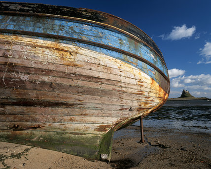 Close-up view of boat with Lindisfarne Castle on Holy Island in the background