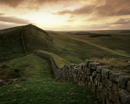 Hadrian's Wall, dark and mysterious under the pink tinged sky, by the light of the setting sun