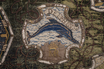 A motif from the Marian Needlework at Oxburgh Hall showing a dolphin with the initials MR