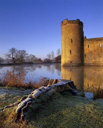 A turret of Bodiam Castle viewed across the moat, with a frosty tree stump on the bank in the foreground