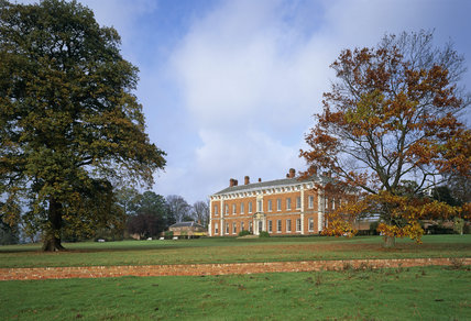 The south front of Beningbrough Hall seen across the lawns in autumn with grey clouds in an otherwise blue sky