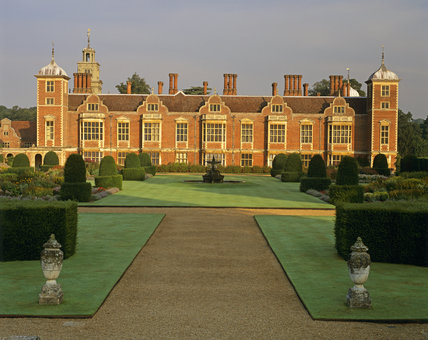 The East front of Blickling Hall, bathed in sunlight, with the formal lines and topiary of the Parterre Garden in the foreground