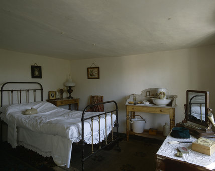 Interior of the Fenman's Cottage at Wicken Fen furnished as it might have been in 1930s with a brass bed with white linen, dressing table and wash stand