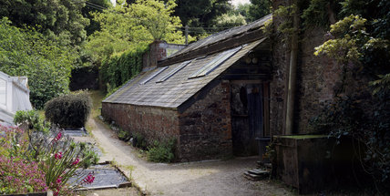 Panoramic view of the potting shed to the rear of the vine house in the garden at Greenway
