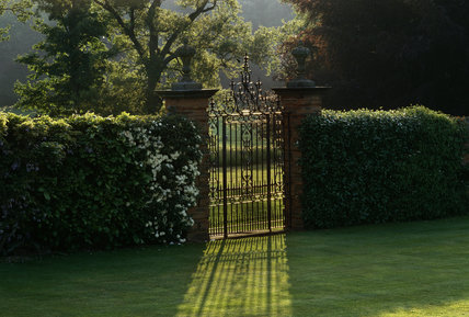 Wrought iron gate to `Carolean' garden which leads out to lake at Packwood House