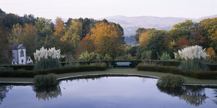 View from the Croquet Terrace towards the lily pond at Bodnant Garden with the range of Snowdonia beyond the Conwy Valley in autumn