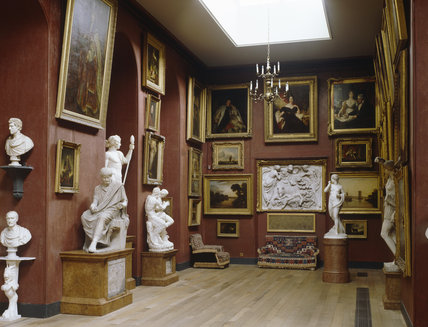 The North Gallery at Petworth, towards the carved marble relief of Dream of Harace by Westmacott, and paintings on the wall, known as the finest surviving expression of early C19th taste