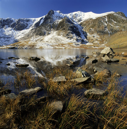 A winter scene of Y Garn with Llyn Idwal in the foreground, the mountains dusted with snow