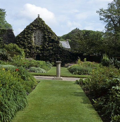The Tythe Barn at Lanhydrock, taken from the herbaceous border Looking along a grass pathway, to a sundial set onto a stone pedestal in a gravel path