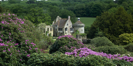 Pink rhododendrons in the foreground make a colourful frame for the remains of Scotney Castle built in the 14th century