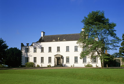 The facade of Ardress House, which is an elegant 17th century farmhouse with a portico over the centrally-placed main entrance
