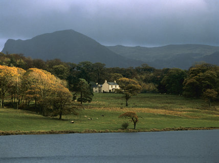 Looking across Crummock Water in the Buttermere Valley to a white farmhouse shrouded by misty grey hills