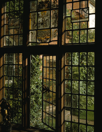 Packwood House, looking out of the Parlour window, the nine panels of stained glass came from various places and are mostly C17th