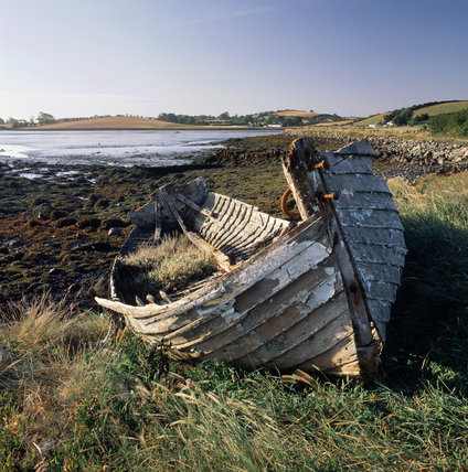 An abandoned and rotting shell of a boat lying on the foreshore of Ballymorran Bay in Strangford Lough