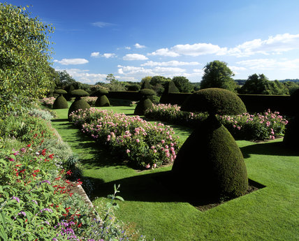 View of the gardens to the south of the house at Hinton Ampner, Hampshire, with topiary, lawns and flowers