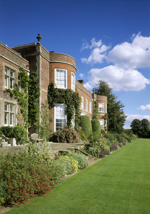 View of the south side of the house at Hinton Ampner, Hampshire, showing the lawn, borders and patio