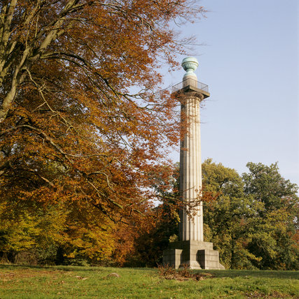 View of the Monument, erected in 1832 to the Duke of Bridgewater in the Ashridge Estate, with a colourful autumnal tree in the foreground