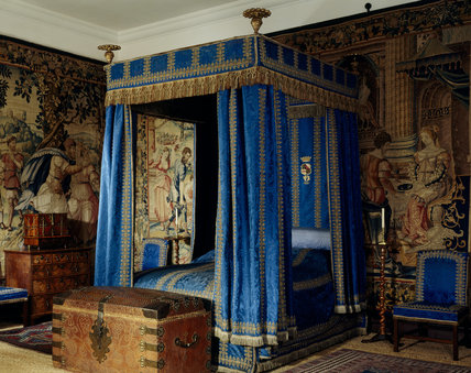 The Blue Bedroom showing the magnificent four poster bed with its vivid blue hangings