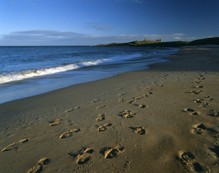 Footprints across the sands of Embleton Bay, with a distant view of the ruins of Dunstanburgh Castle sitting on its mound