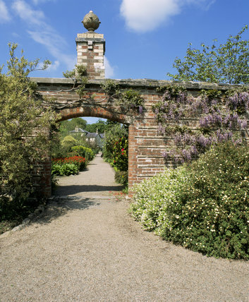 Rowallane, the outer walled garden looking to the walled garden with mauve wisteria draping the wall
