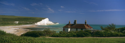 The Seven Sisters seen across the deserted beach, with white washed cottages, owned by the Trust, in the fore-ground